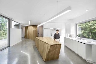 Bernier's firm designed the built-in storage, seating area, and kitchen island to be intentionally abstract, directing attention to the forest outside. Cabinetmaker Pixel & Scie manufactured the furniture.