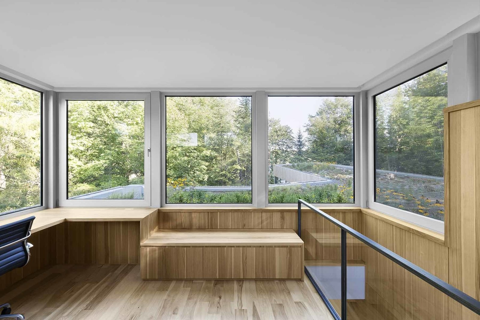 A small box atop the home looks out onto a green roof, designed by local landscaping firm Toits Vertige.  House of Lake Grenier by Tiffany Jow