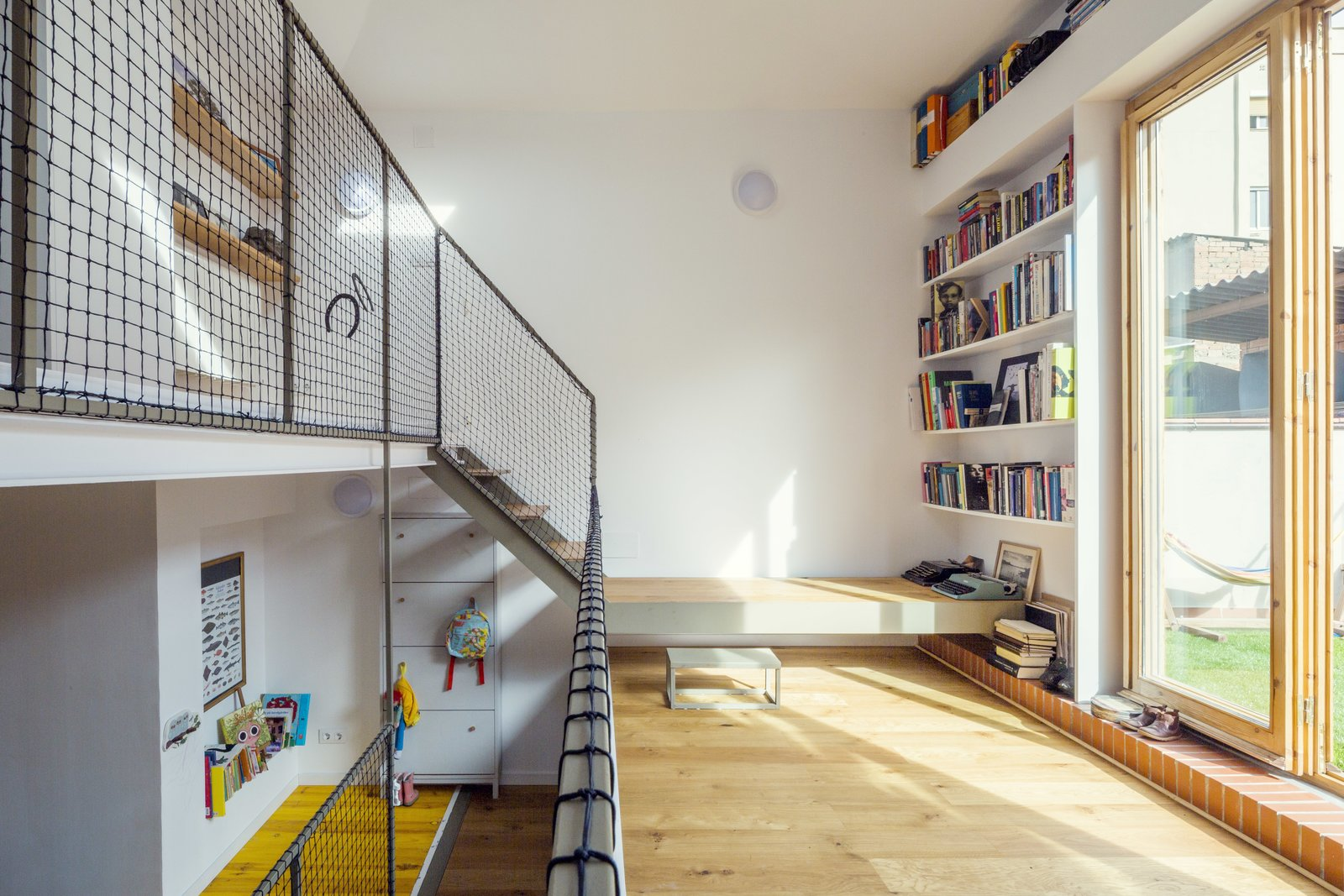 The railings on the middle level are 1.2-by-1.2-inch wrought iron bars and the wood flooring is by Kahrs.  A 16-Foot-Wide Barcelona Row House Gets Creative to Stay Bright and Airy by Alex Vuocolo from Surrounded on Nearly All Sides? These Homes Tackled Tough Sites and Won