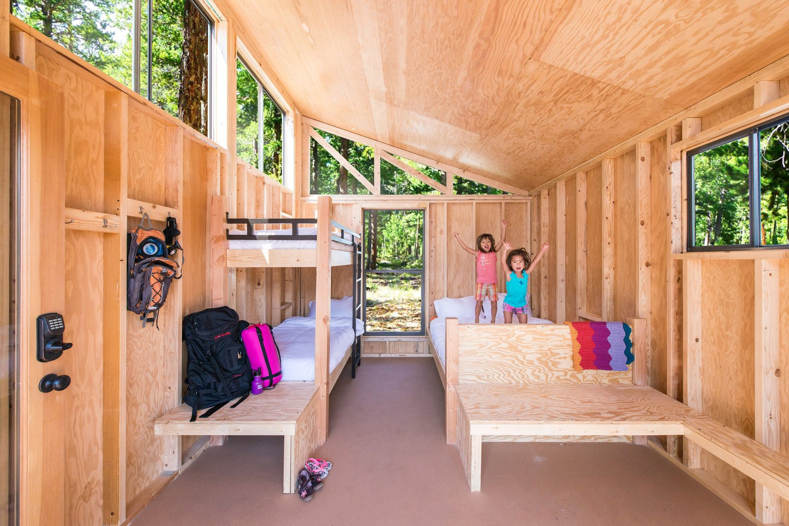 Bedroom, Bunks, Bed, and Chair Designed by Cal Poly Pomona students, this factory-built Wedge cabin prototype features plywood interiors for a raw and rustic vibe.   Photo 2 of 5 in Modern Prefab Cabins for California State Parks