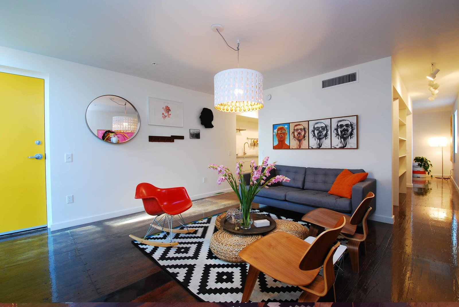 Living Room, Dark Hardwood Floor, Chair, Pendant Lighting, Coffee Tables, Ottomans, Track Lighting, and Sofa The lone furnished unit, which is slated to be an Airbnb rental, features a RAR rocker and two LCW chairs by Charles and Ray Eames.  Shipping Containers by Dwell