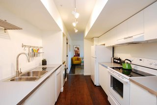 The galley kitchen, which includes a washer/dryer combo, separates the living room and bedroom.