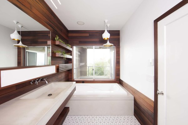 "In order to give the redesign a seamless feel, Brigham and Archuleta carried the use of wood throughout the room—including the shower. Archuleta researched types of wood that can withstand a high-moisture environment, and the most visually appealing was coastal redwood. He came across an unlikely source of reclaimed redwood: old pickling vats from a company called Trestlewood.   Experience in working with reclaimed wood taught Archuleta that ""wood that's been exposed to liquid for long periods of time pulls in minerals that it wouldn't naturally have access to in its living state."" In this case, the iron bands and nails that held the barrels together reacted with the pickling liquid, leaving behind a rich, dark patina."