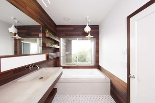 """In order to give the redesign a seamless feel, Brigham and Archuleta carried the use of wood throughout the room—including the shower. Archuleta researched types of wood that can withstand a high-moisture environment, and the most visually appealing was coastal redwood. He came across an unlikely source of reclaimed redwood: old pickling vats from a company called Trestlewood.   Experience in working with reclaimed wood taught Archuleta that """"wood that's been exposed to liquid for long periods of time pulls in minerals that it wouldn't naturally have access to in its living state."""" In this case, the iron bands and nails that held the barrels together reacted with the pickling liquid, leaving behind a rich, dark patina."""