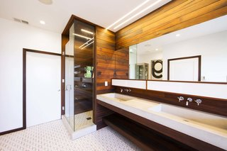 "The entire bathroom is based on a grid, informed by Brigham's background in graphic design. The 4"" redwood slats form the base measurement; the height of the sink, the bath, and all other features are built in multiples of four. Each piece was designed to either project from or recess back into the wall, continuing seamlessly into the next fixture. Everything from the medicine cabinet to the planters floats off the ground, opening the space."