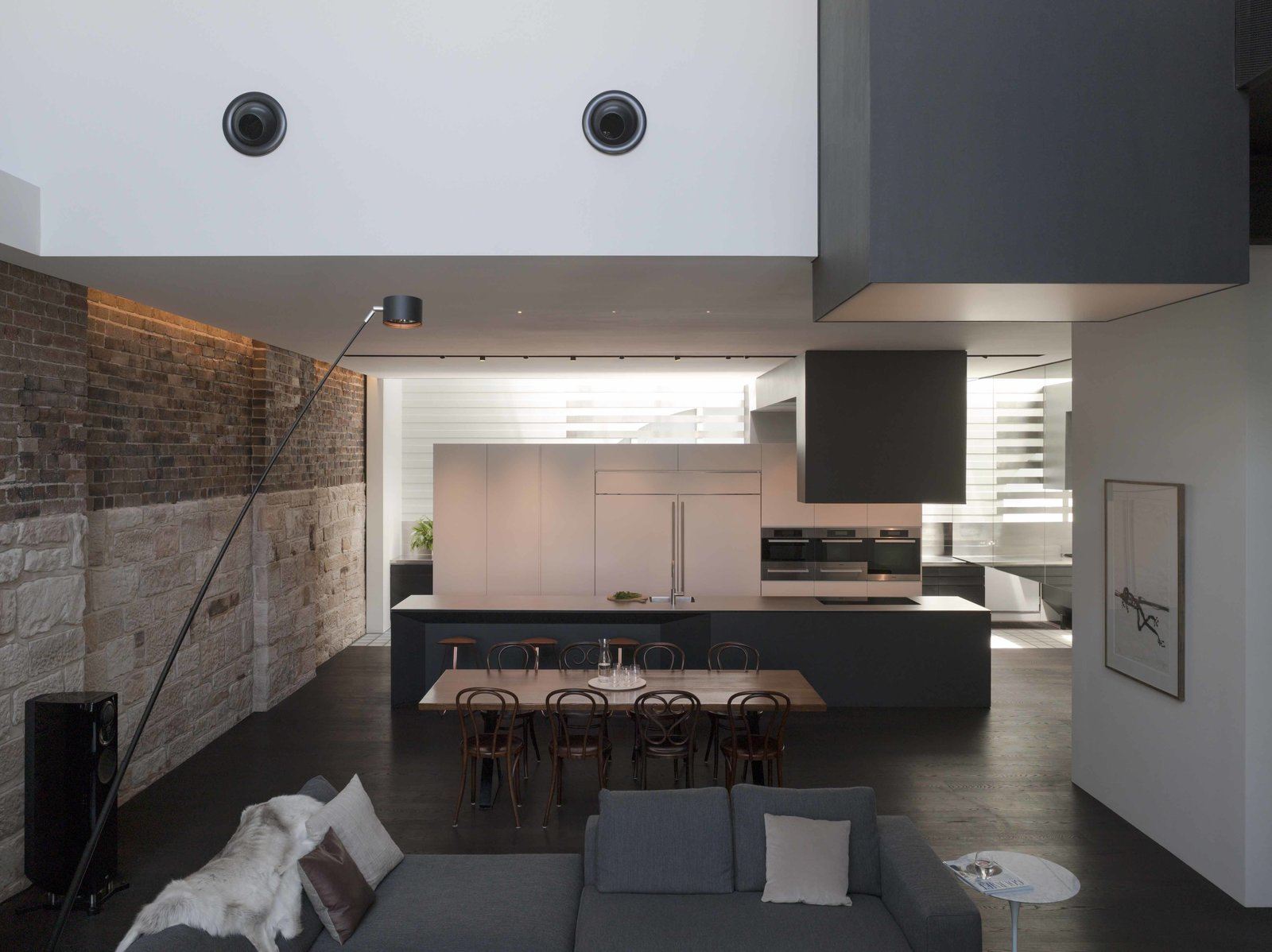 """The kitchen is accessible from a raised courtyard across from the main living space. """"The double exhaust hood looks like an old industrial gantry,"""" remarks Cashman. Sandblasted brick and sandstone from the original warehouse dialogue with floating white and grey cabinetry.  Photo 2 of 7 in An Airy Sydney Home Goes Vertical to Gain Space"""