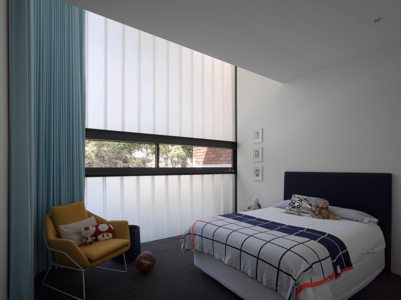 A secondary bedroom meant for a child has a partially translucent, curved glass wall.  Photo 6 of 7 in An Airy Sydney Home Goes Vertical to Gain Space