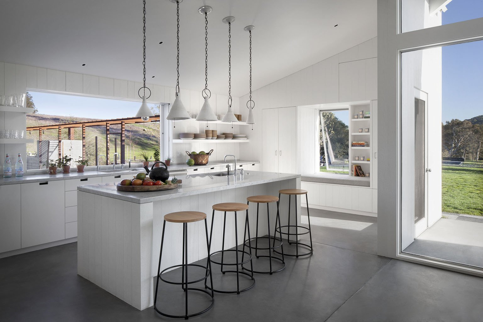 Carrara marble countertops by Franke spread through the kitchen around two sinks. Custom doors by Liberty Valley connect the common rooms to the backyard.  A LEED Platinum Family Home Takes the Place of an Abandoned California Farmhouse  by Kelly Dawson