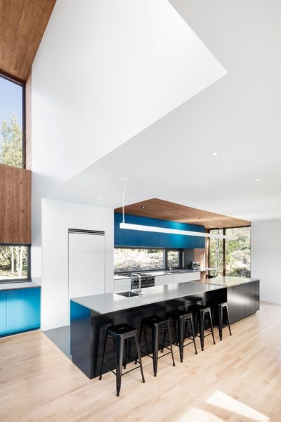 Since one of the homeowners is passionate about food and cooking, Rasselet made an oversized kitchen the focal point of the home. Hudson iron counter stools from Structube sit beneath a suspended MicroSquare LED fixture from Philips Ledalite.