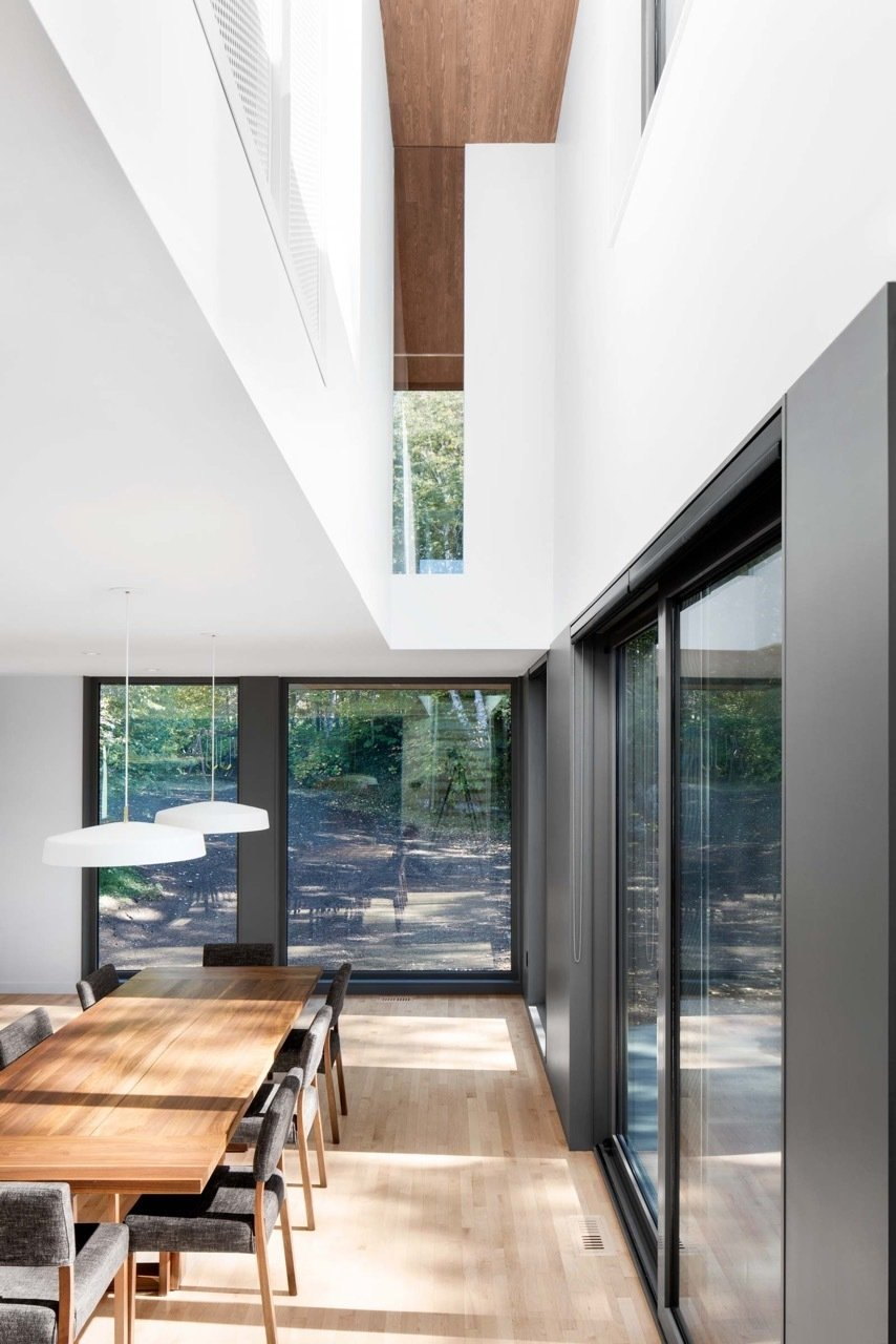"""""""Conceptually, all of the spaces in the house are connected to the kitchen and dining area by the stairwell, the second-floor catwalk, or through the glass in the living room,"""" said Rasselet. The dining room's walnut table and chairs are by Atelier LC2, and the Cliff light fixture is by Lambert & Fils.  Lounge from House of the Week: Splash of Color in an Otherwise Minimalist Home"""