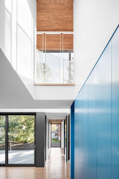 Natural maple wood is used as flooring material throughout the home, and double-glazed Shalwin windows fill each space with light. The second level's catwalk is protected by perforated steel, painted white, by Enfer Design.
