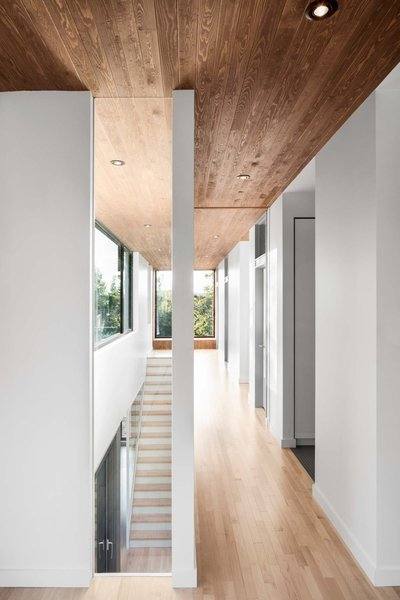 A ceiling of stained cedar lines the hallway of the second level. The home features three bedrooms on the second floor, and a ground-level playroom that can be converted to a private sleeping area when guests arrive.