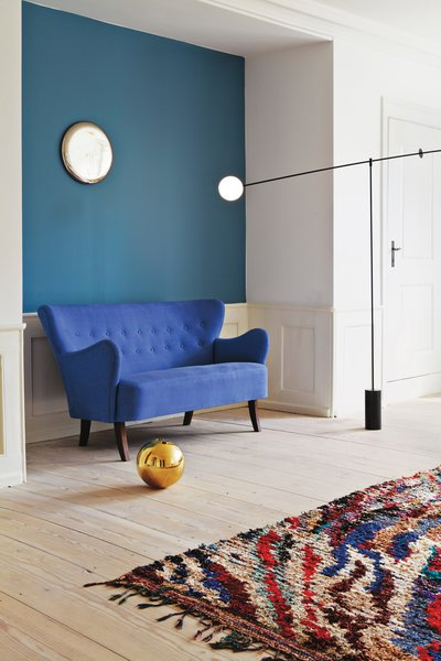 A Danish sofa, designer unknown, is set against an accent wall painted in Stone Blue by Farrow & Ball. As the local dealer for Anastassiades, the Apartment contains various pieces of his work, including the Mobile Chandelier 5 (2011), the Ball vase in cast brass (2006), and the wall-mounted Beauty Mirror (2010). The vintage Boucherouite rug is from Morocco. Photos courtesy the Apartment.