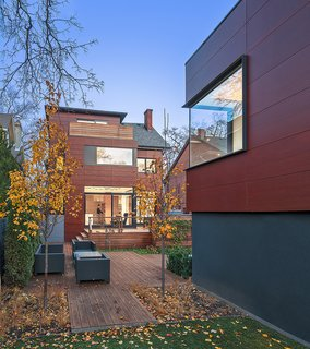 """The Parklex facade visually connects the main house and coach house. """"We wanted to use an exterior material that harmonized with the house's context, which is an older neighborhood filled with Victorian houses made of Toronto red clay brick,"""" architect Heather Dubbeldam says."""