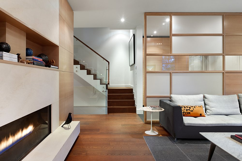 """""""The material choices for the interior were not directly influenced by the facade, but we did use fumed oak flooring throughout the house, and its deep reddish color picks up on some of the tones present in the exterior,"""" Dubbeldam says. The couple selected a mix of contemporary furniture and modern classics like the Saarinen side table.  A Cramped Boarding House Transformed Into an Open, Modern Home in Toronto by Sam Elmore"""
