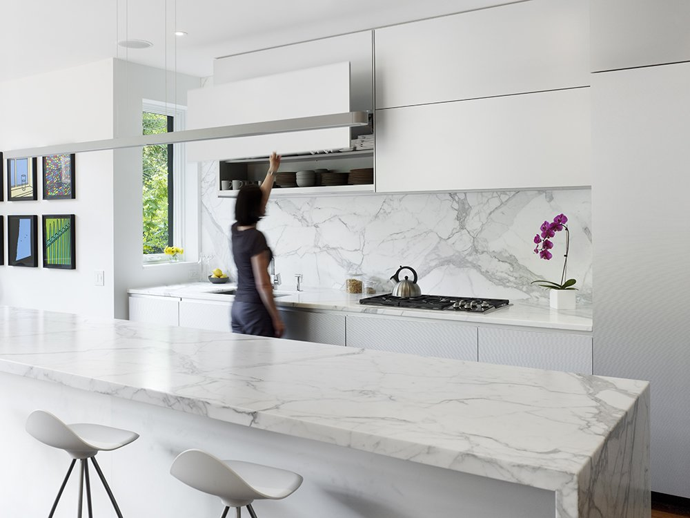 Kitchen, Marble Counter, White Cabinet, Recessed Lighting, Undermount Sink, Metal Cabinet, Pendant Lighting, Medium Hardwood Floor, Marble Backsplashe, and Cooktops The kitchen contains Onda barstools by Stua from Design Within Reach that surround a 13-foot Calacatta marble island. Custom white aluminum cabinets float above the kitchen appliances by Miele with a stovetop from Wolf and a range hood by Airmec Bello.  A Cramped Boarding House Transformed Into an Open, Modern Home in Toronto by Sam Elmore