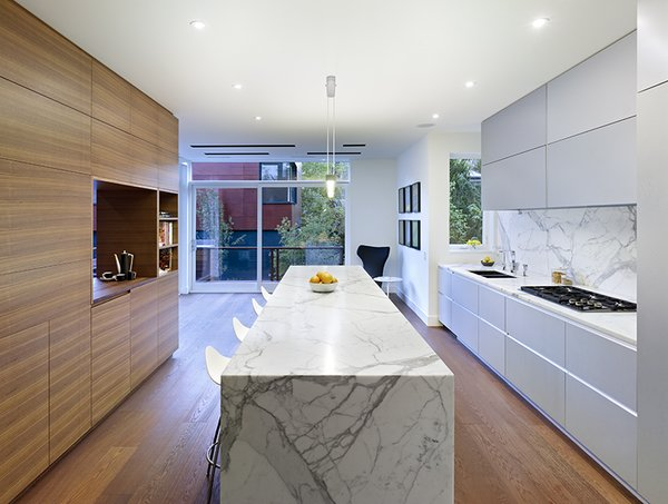 """The walnut unit between the kitchen and dining room ties into the fumed oak floor,"" Dubbeldam says. ""The rest of the materials in the house—glass, marble, stone—were selected to offset the wood."""