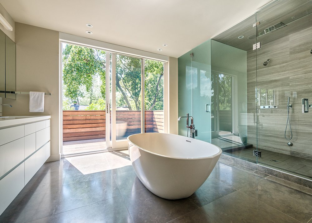 The master bathroom features a Wetstyle bathtub and Mare Bianco limestone walls.  A Cramped Boarding House Transformed Into an Open, Modern Home in Toronto by Sam Elmore