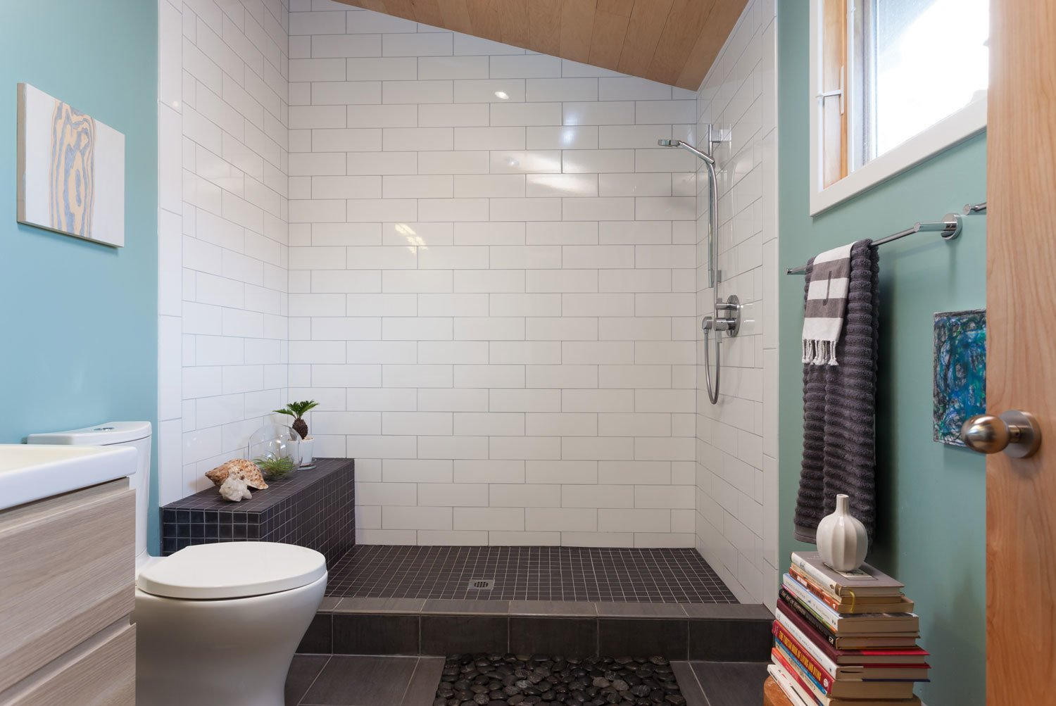 Bath Room, Open Shower, Two Piece Toilet, and Subway Tile Wall The bathroom features white and black tile and a small rock bed.  Photo 4 of 5 in Renovation: A Sunny Berkeley Bungalow Invites the Outdoors In from Sunny Berkeley Bungalow Renovation