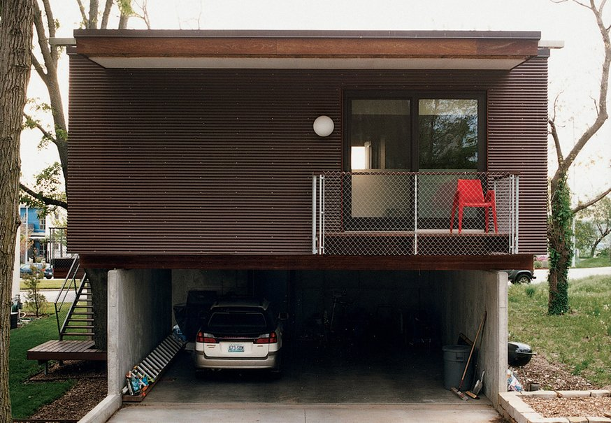 """Architect Jamie Darnell had a simple plan for his family's home in Kansas City, Missouri, but the result is anything but plain. Wrapped in corrugated copper, the house has a frontier-cabin quality that's evolving with age. At first it was as shiny as a penny, but that's changing. """"My house looks like it has a skin disease,"""" Jamie says. """"It's just oxidizing in a weird way. Eventually it'll go green. This is just the first stage of the patina.""""  Minimalist Facades We Love by Zachary Edelson"""