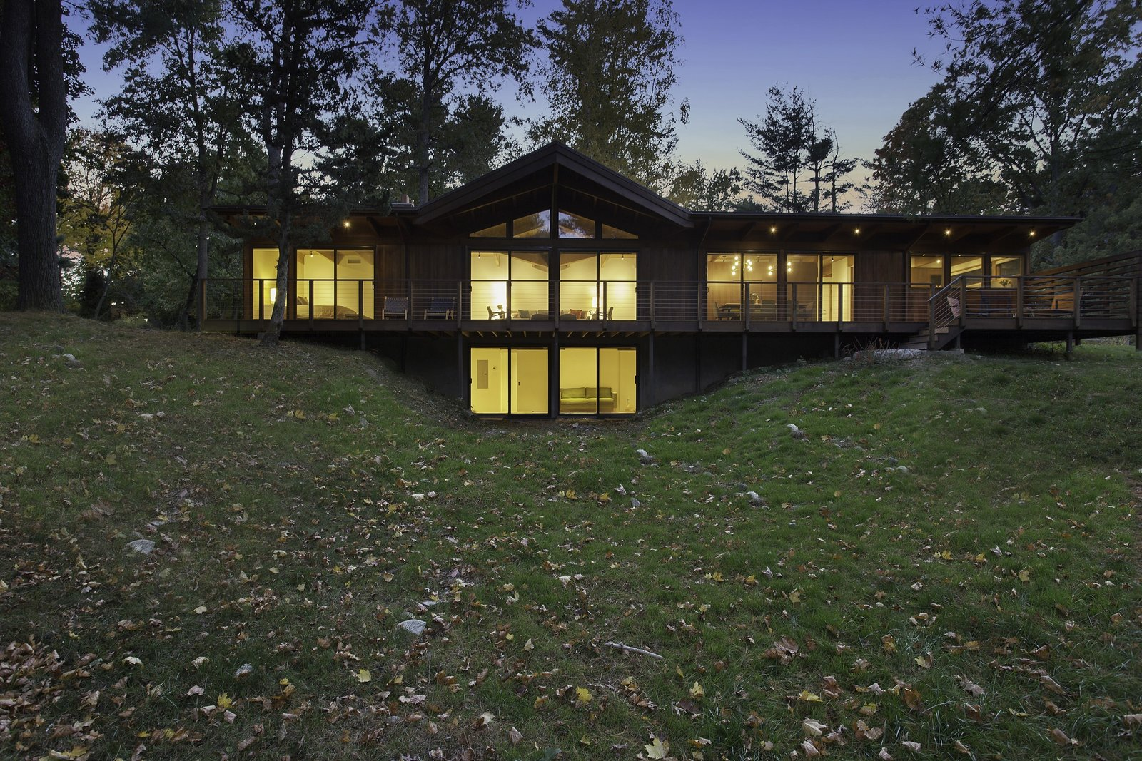 """""""The use of the structural insulated panels for the roof allowed us to keep the exposed post-and-beam look, which is a midcentury trademark, while making the house energy-efficient,"""" Schultz said. Douglas firm beams and soffits support a SIPS roof, which shades Andersen Windows & Doors. The deck, made of red meranti, overlooks a nearby pond.  City Skyline by Kelly Dawson"""