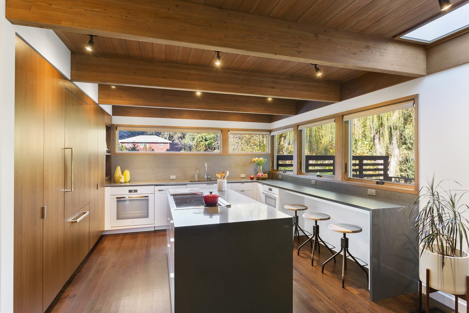 Custom cabinetry with a walnut veneer is across from Caesarstone countertops and a Basaltina tile backsplash by Stone Source.  City Skyline by Kelly Dawson