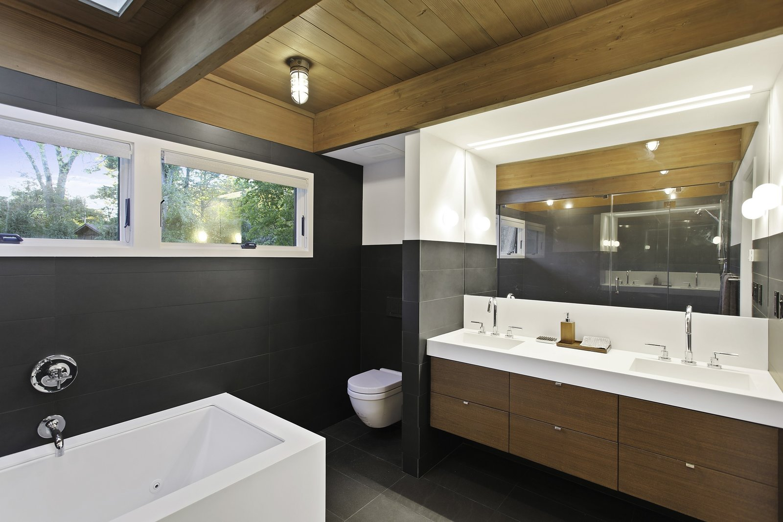 A custom Corian Glacier White countertop finishes a custom vanity made of stained American walnut. Corian also supplied the rectangular sinks, which are topped with Cigno faucets by Lacava. The bathtub is by Zuma, and it stands on a Corian platform.  City Skyline by Kelly Dawson