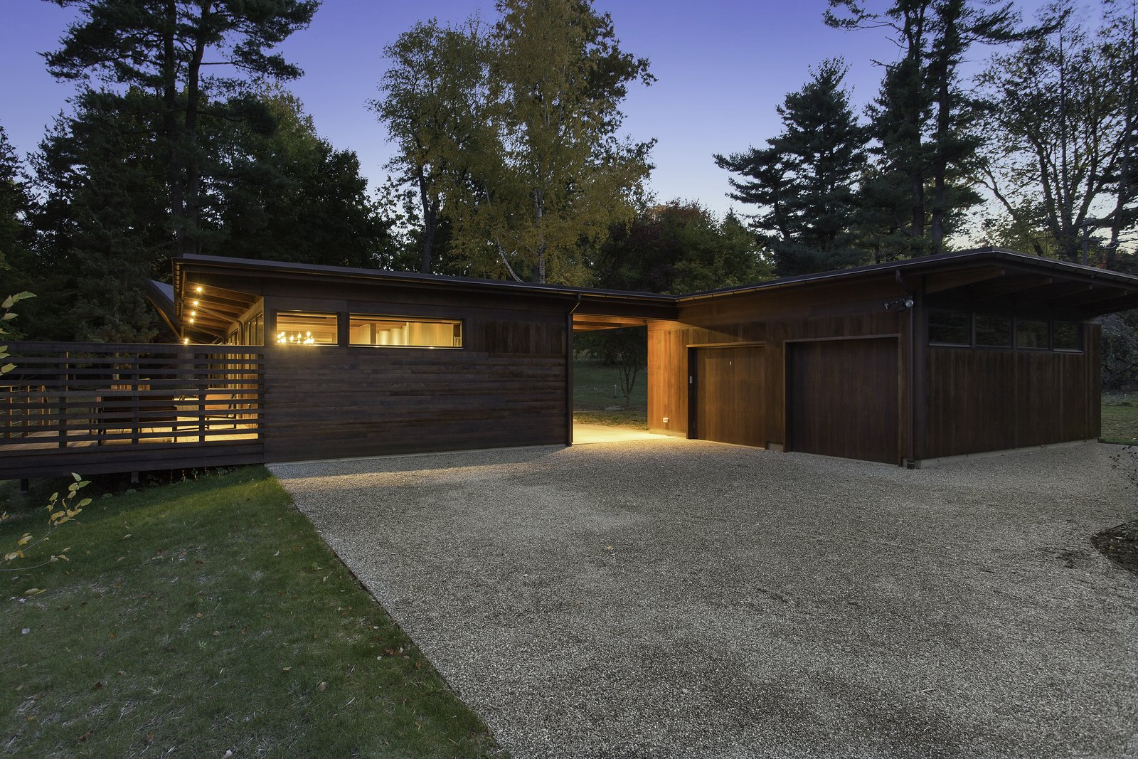 Stained western red cedar extends around the full exterior of the home. A pea gravel driveway stays in place with a steel edge.  City Skyline by Kelly Dawson