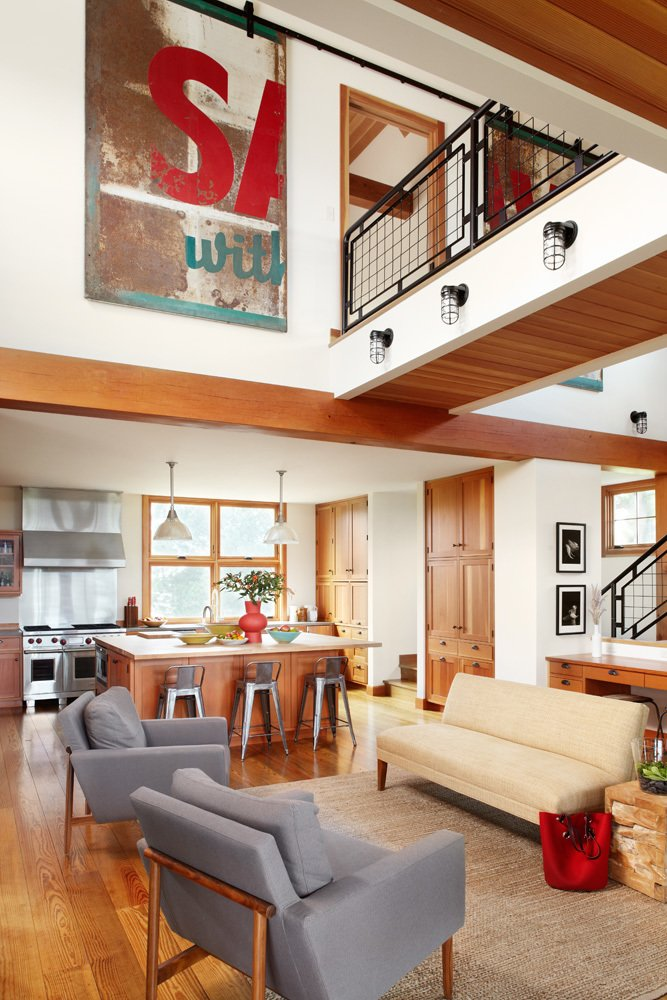 Far from the dark, cavernous barns of the Midwest, tall ceilings and an open floor plan creates an airy interior. Architect Bill Bickford and contractor Traditional Carpentry, Inc. collaborated on a unique sliding door to the upstairs master suite: a vintage billboard cut in half and put on a barn door track. The sitting area below features Raleigh Armchairs from Design Within Reach and a loveseat from Jayson Home.  A Family Salvages an 1880s Barn to Create Their Nearly-Net Zero Escape by Caroline Wallis from House of the Week: An Eco-Friendly Family Retreat Built with Reclaimed Materials