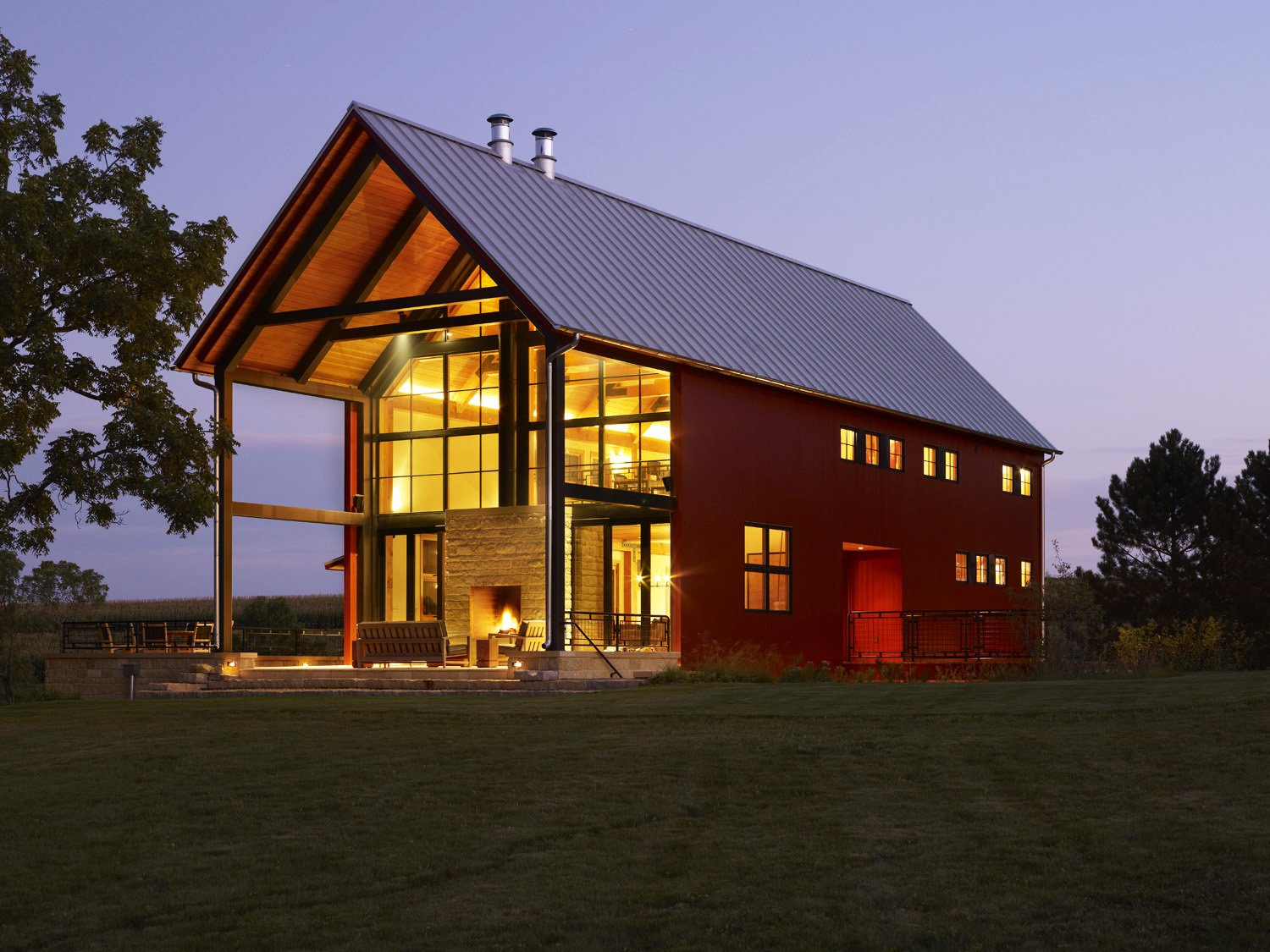 Don't let its traditional silhouette fool you: this home features a grid-tied solar photovoltaic array just south of the property, which supplies the family's annual average powers usage. Large steel beams and columns flank the patio, framing views of the landscape.  A Family Salvages an 1880s Barn to Create Their Nearly-Net Zero Escape by Caroline Wallis from House of the Week: An Eco-Friendly Family Retreat Built with Reclaimed Materials