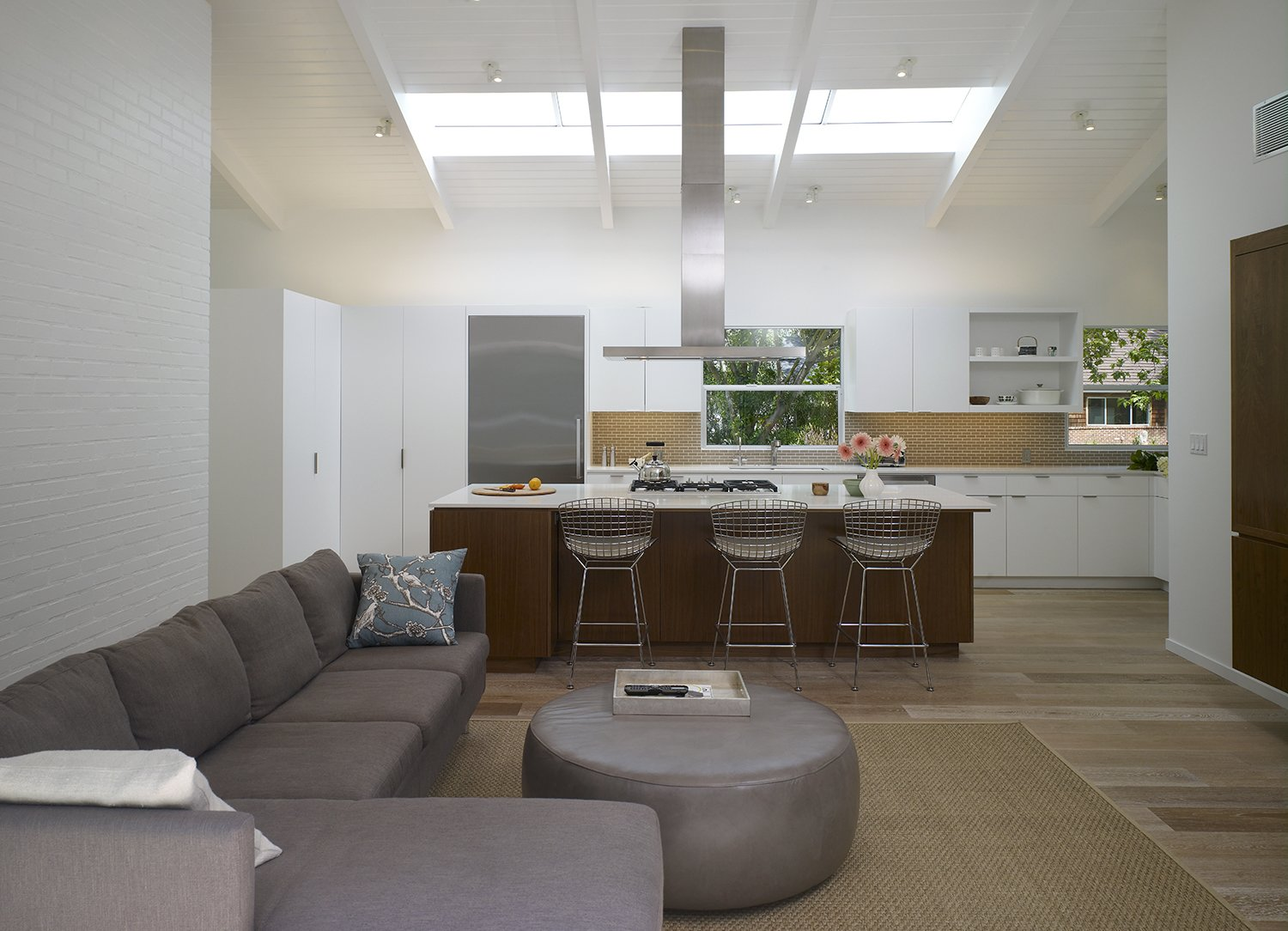 """Kitchen and Light Hardwood Floor Along with the interior design's emphasis on natural light, Montalba also wanted a minimalist look. That sense of """"timelessness,"""" as he says, is achieved with help from the Bertoia counter stools in the kitchen.  Best Photos from A California Ranch Renovation Opens to the Outdoors"""