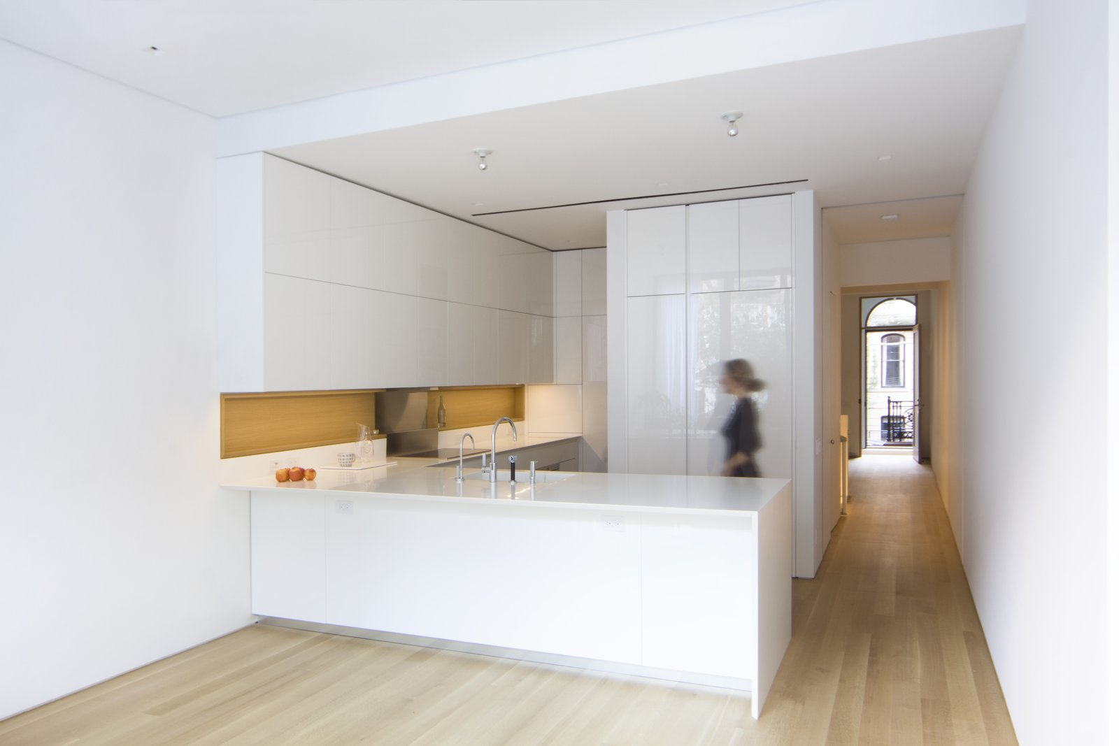 Kitchen, Engineered Quartz Counter, White Cabinet, Light Hardwood Floor, Ceiling Lighting, and Undermount Sink The kitchen has views to the historic main entrance and features lacquered cabinets and an integrated wooden niche custom-designed by the architects with GD Cucine. Matching Corian countertops and an integrated sink maintain a minimal aesthetic alongside appliances by Gaggenau and Miele.  White Oak by Maura Lucking