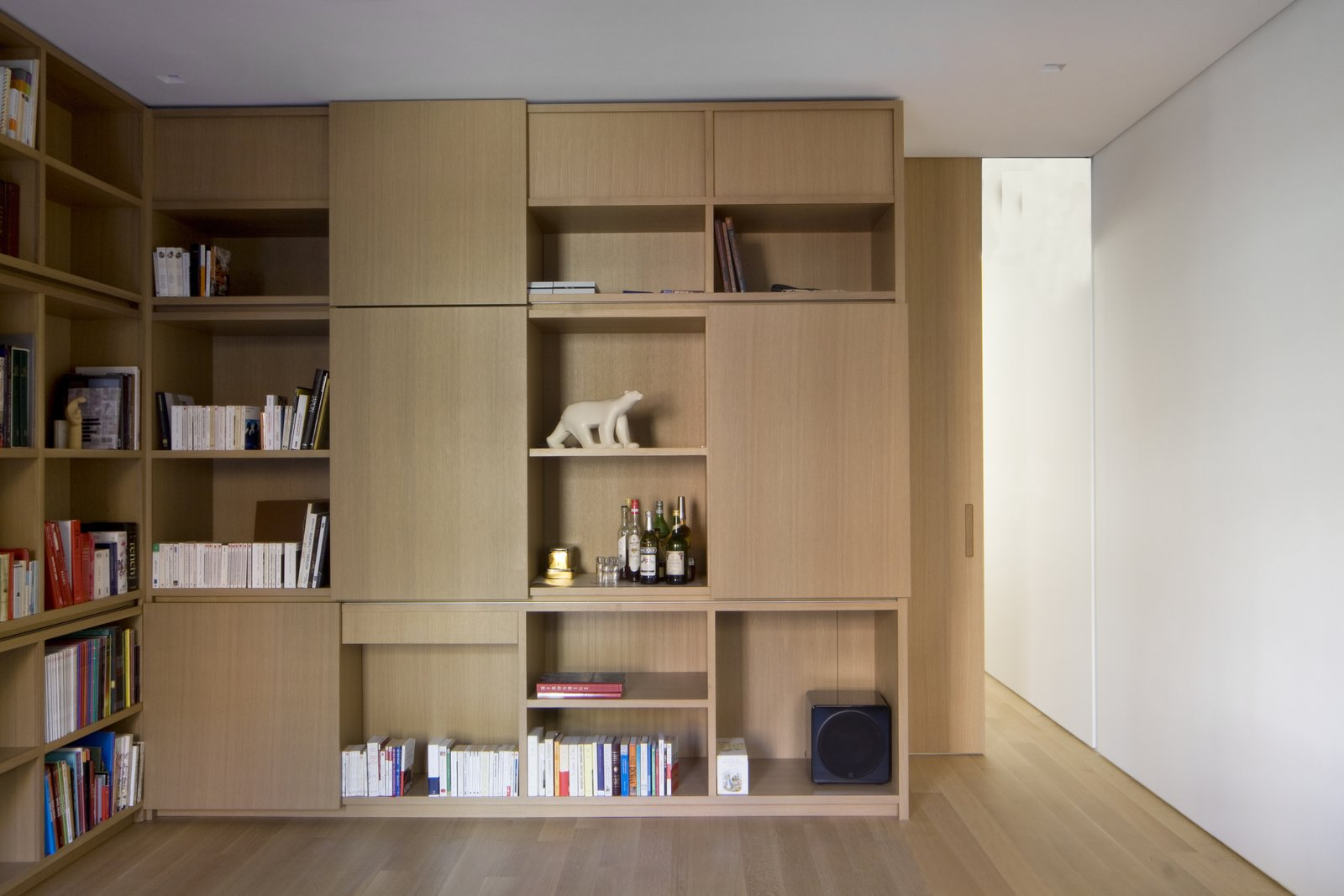 Storage Room and Shelves Storage Type More custom millwork features asymmetrical shelving and closed storage spaces with sliding panels on HAFELE sliding tracks. A 10-inch matching pocket door provides privacy when desired without interrupting the space.  White Oak by Maura Lucking