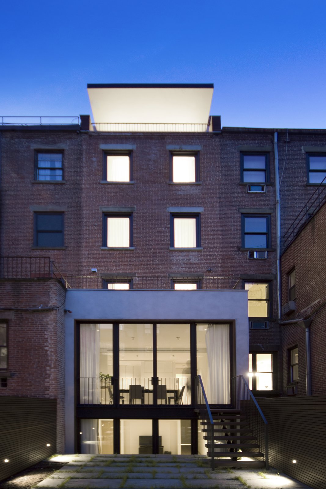 The restored brick rear facade contrasts with the extended footprint of the first two floors and a dramatic cantilevered penthouse roof. Blue stone pavers, infilled with grass, finish the patio while a black steel stair leads to the kitchen.  New York City Row House Renovations We Love by Zachary Edelson from White Oak