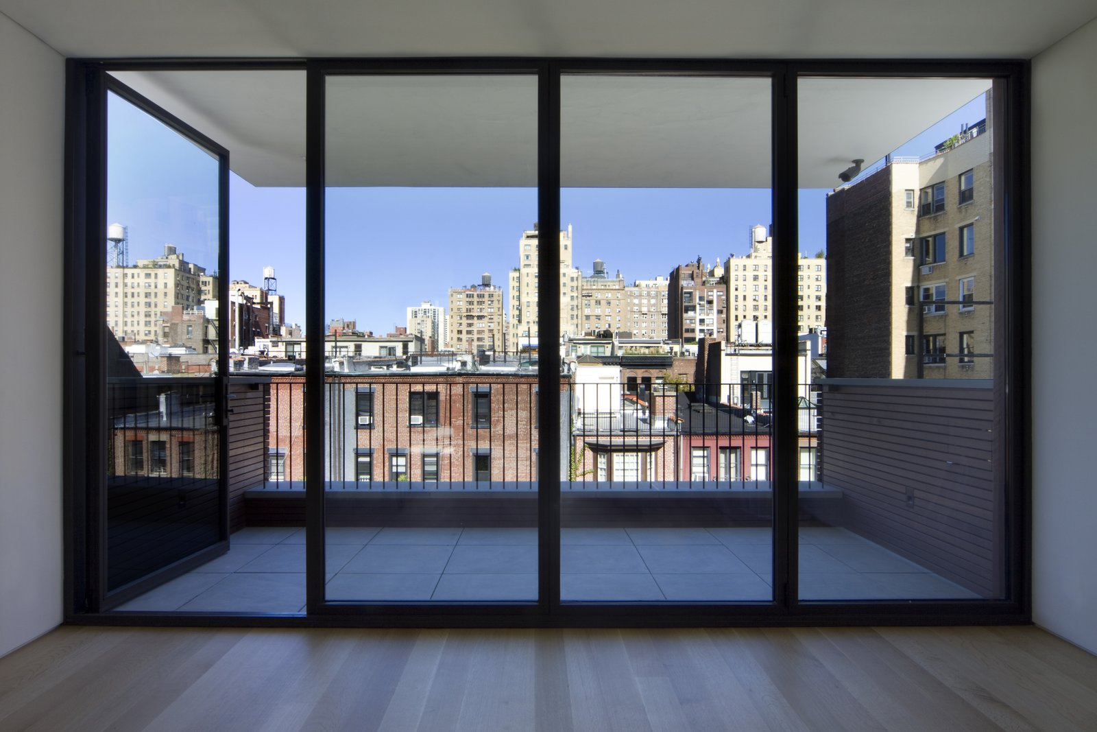 """The fifth story was added late in the design process because """"our clients wanted to have their own private space,"""" Ruggieri says. The stunning north view across Manhattan from the penthouse is one of the home's best features, outlined in black steel windows by Optimum.  White Oak by Maura Lucking"""