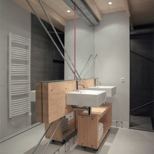 Two large mirrors cover the wall in the bathroom. A small pine box on wheels holds towels.