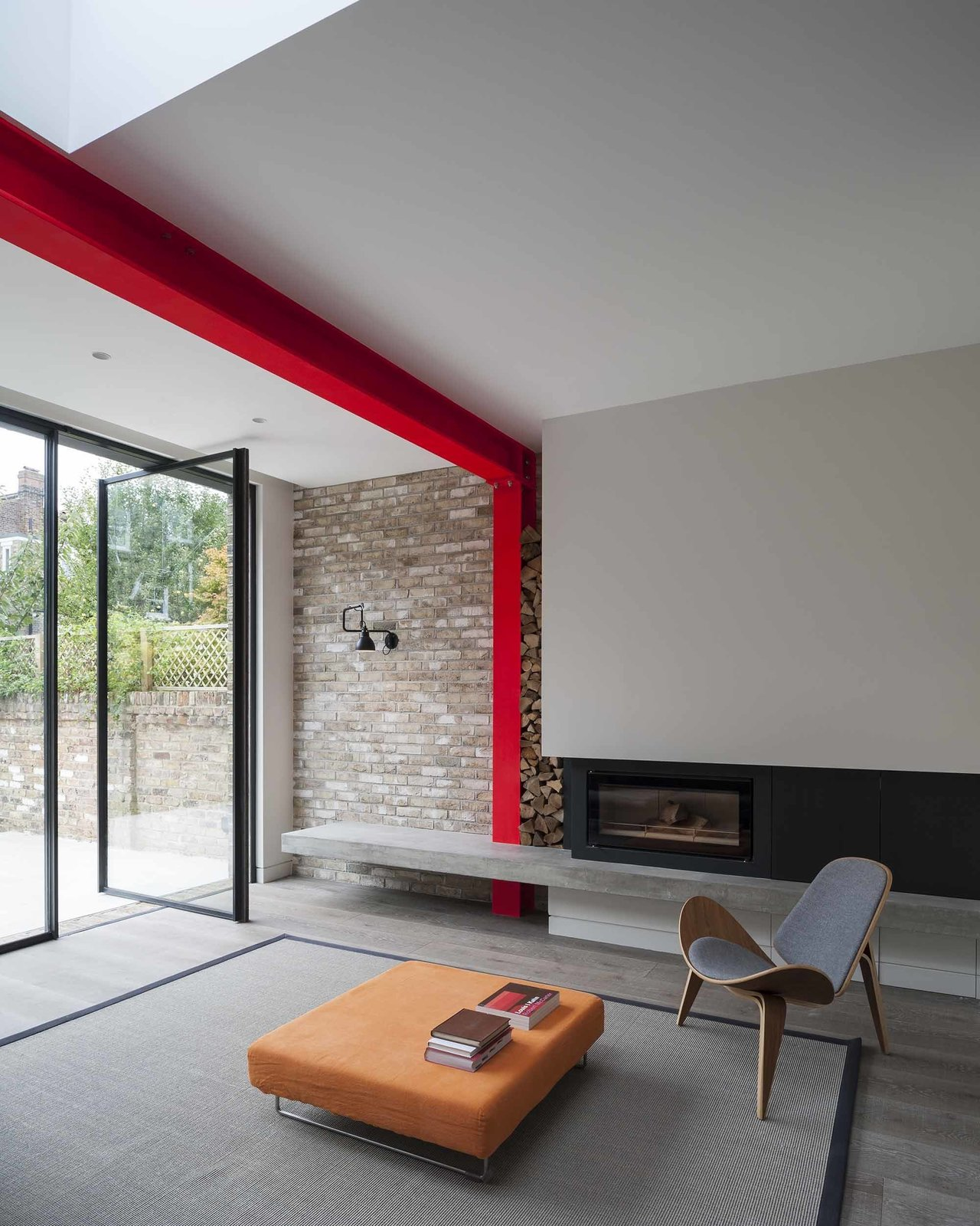 A Hans Wegner Shell chair by Carl Hansen & Søn outfits the living room, which is defined by a steel beam painted sharp red.  97+ Modern Fireplace Ideas from A London Town House Renovation Beaming with Personality