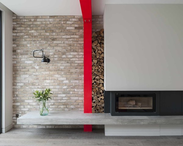 Tigg Coll Architects took a new approach to a straightforward town house renovation and expansion in London. The home's rear extension has its own personality, with with pivoting glass doors, sharp red support beams, and a wood-burning fireplace. The overhanging concrete plinth acts as a hearth or, as Tigg imagines it, a sort of contemporary inglenook. Wood piles neatly between the beam and wall. The fireplace, a Stovax Riva 2, is flanked by a Lampe Gras wall lamp; firewood is cleverly stored in the narrow space between the fireplace and the red support beam, creating a fun moment of practical texture in the room.