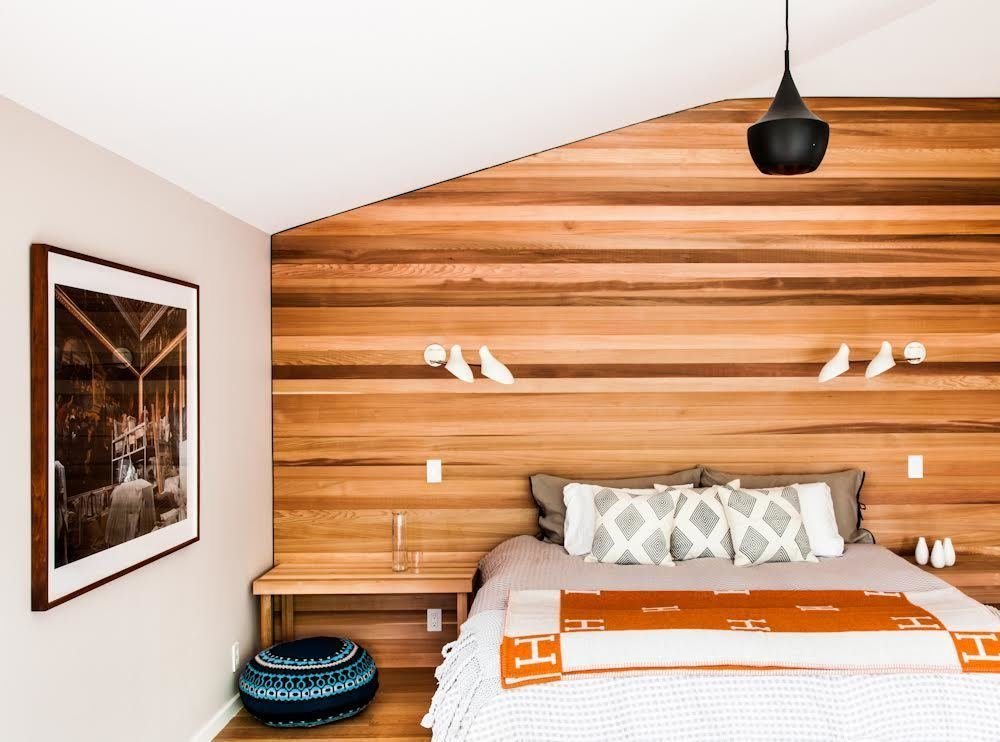 """We brought the cedar siding of the exterior inside strategically, both to blur inside and out and to give texture,"" Young says. ""Simple forms and clean lines, if done right, have a calming effect and nicely contrast the furnishings."" The master bedroom features the same western red cedar as the exterior, and lighting by David Weeks Studio.  Photo 2 of 12 in Material Spotlight: 11 Hardworking Uses of Western Red Cedar from A Renovation Simplifies Life at a Wood Beach House in the Hamptons"