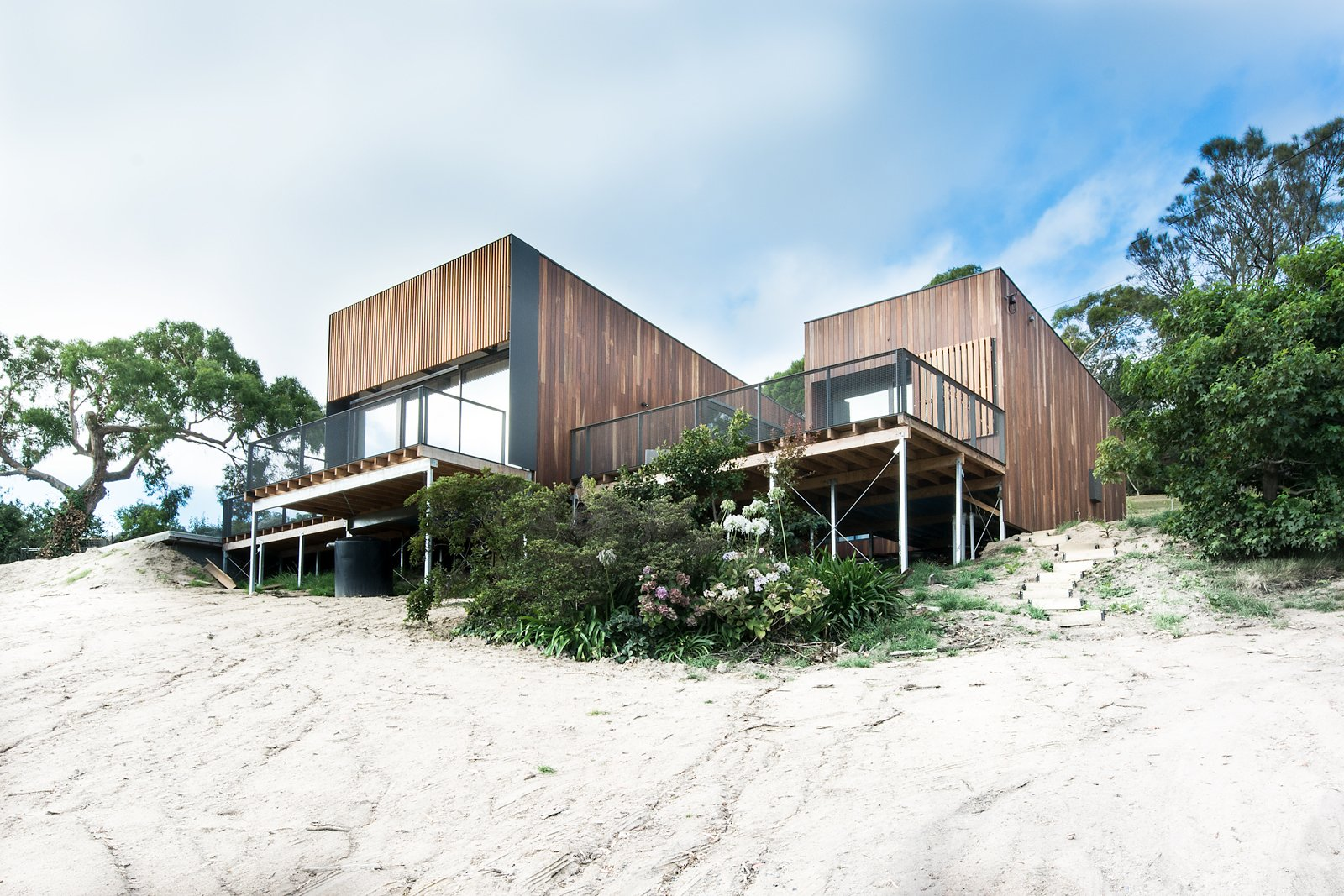 """Exterior, Beach House Building Type, House Building Type, Flat RoofLine, and Wood Siding Material The home, clad in natural Australian timber, enjoys a sense of lightness thanks to slender columns that let it float over the dunes. The driveway and entry, at the rear of the building, have an understated design to build to the interior's magnificent ocean views. Firm director Phil Snowdon explains, """"By creating an architectural form that draws your eye and leads you up the steep driveway, we could engage new visitors in a welcoming process that first reveals the object and then slowly reveals the main event, being the view.""""  Photos from Martha"""
