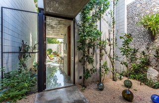 Several courtyards help bring greenery in. On the west side of the home, plants absorb sunlight and create another passive cooling feature. Crushed limestone pebbles and an exposed stone wall complete the lush space.