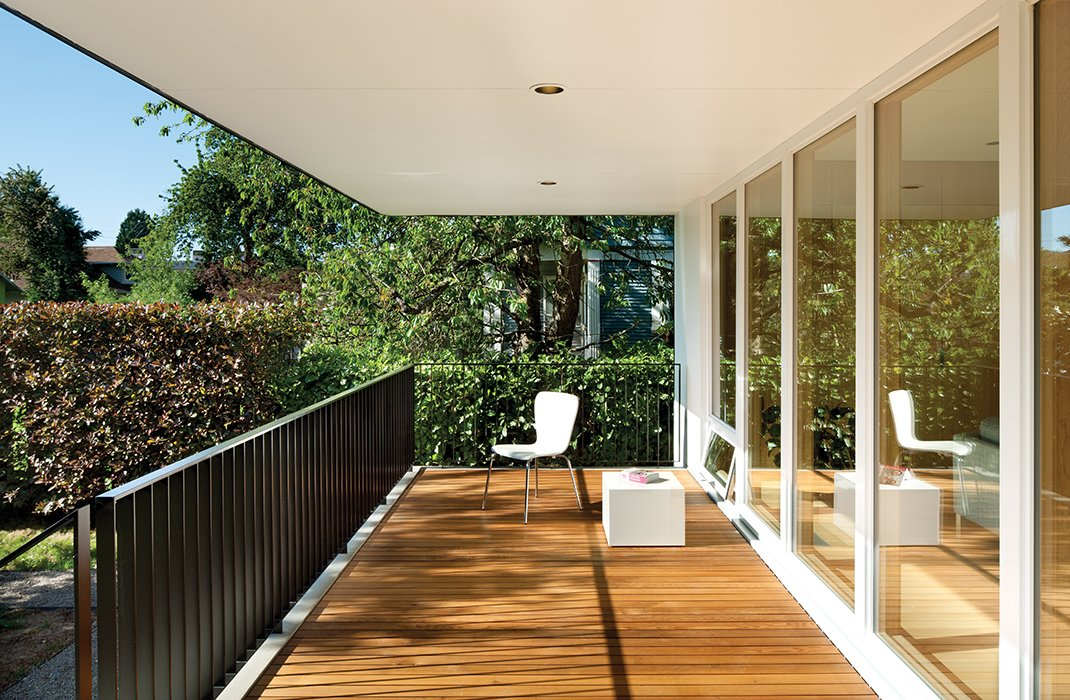 """Outdoor and Wood Patio, Porch, Deck Floor-to-ceiling windows from Sierra Pacific offer views across a cedar deck to the backyard. Oakley says he and Waechter asked themselves, """"How would we build something that's functional and warm and utilitarian, and have some vestige of familiar architectural reference?""""  Photo 6 of 9 in An Industrial Designer's House Blends Economy and Simplicity"""