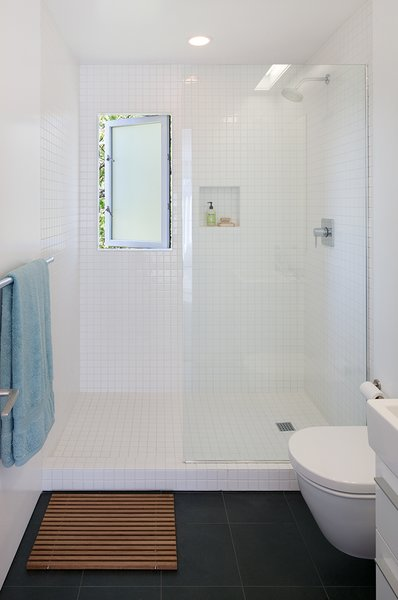 The master bathroom is clad in inexpensive tile from Daltile. The wall-hung toilet is by Duravit.  Photo 7 of 9 in An Industrial Designer's House Blends Economy and Simplicity