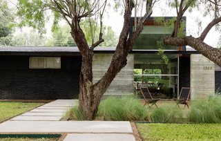 When renovating a house in McAllen, Texas, for his brother-in-law's family, architect Luis López designed an overhang with concrete beams that protects the front entrance from the area's frequent rain. A large front window was inserted to provide views through the house to the backyard.