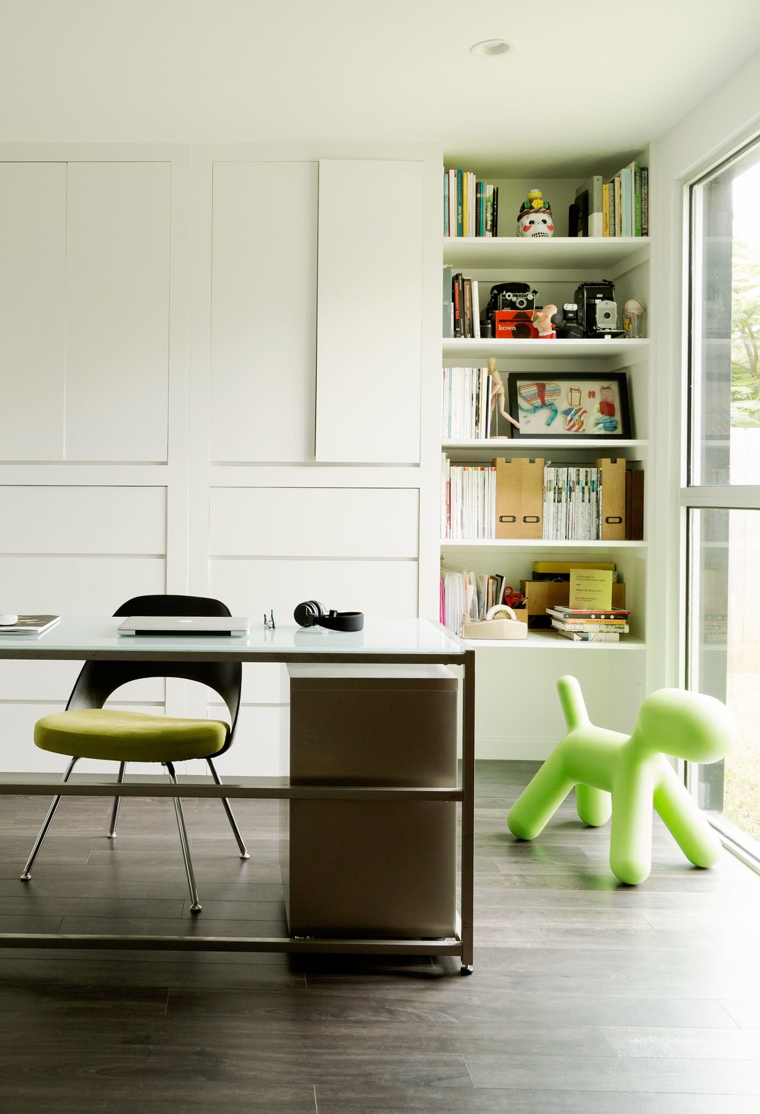 Office, Chair, Desk, Storage, Bookcase, Shelves, Dark Hardwood Floor, and Study Room Type The office space doubles as a play area, so the parents can keep an eye on the kids while they work. The Saarinen Plastic Back side chair from Knoll was a gift from a friend.  Photo 3 of 10 in A Modern Renovation Connects to a Traditional Texas Town Through a Glass Wall