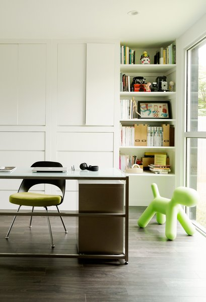 The office space doubles as a play area, so the parents can keep an eye on the kids while they work. The Saarinen Plastic Back side chair from Knoll was a gift from a friend.
