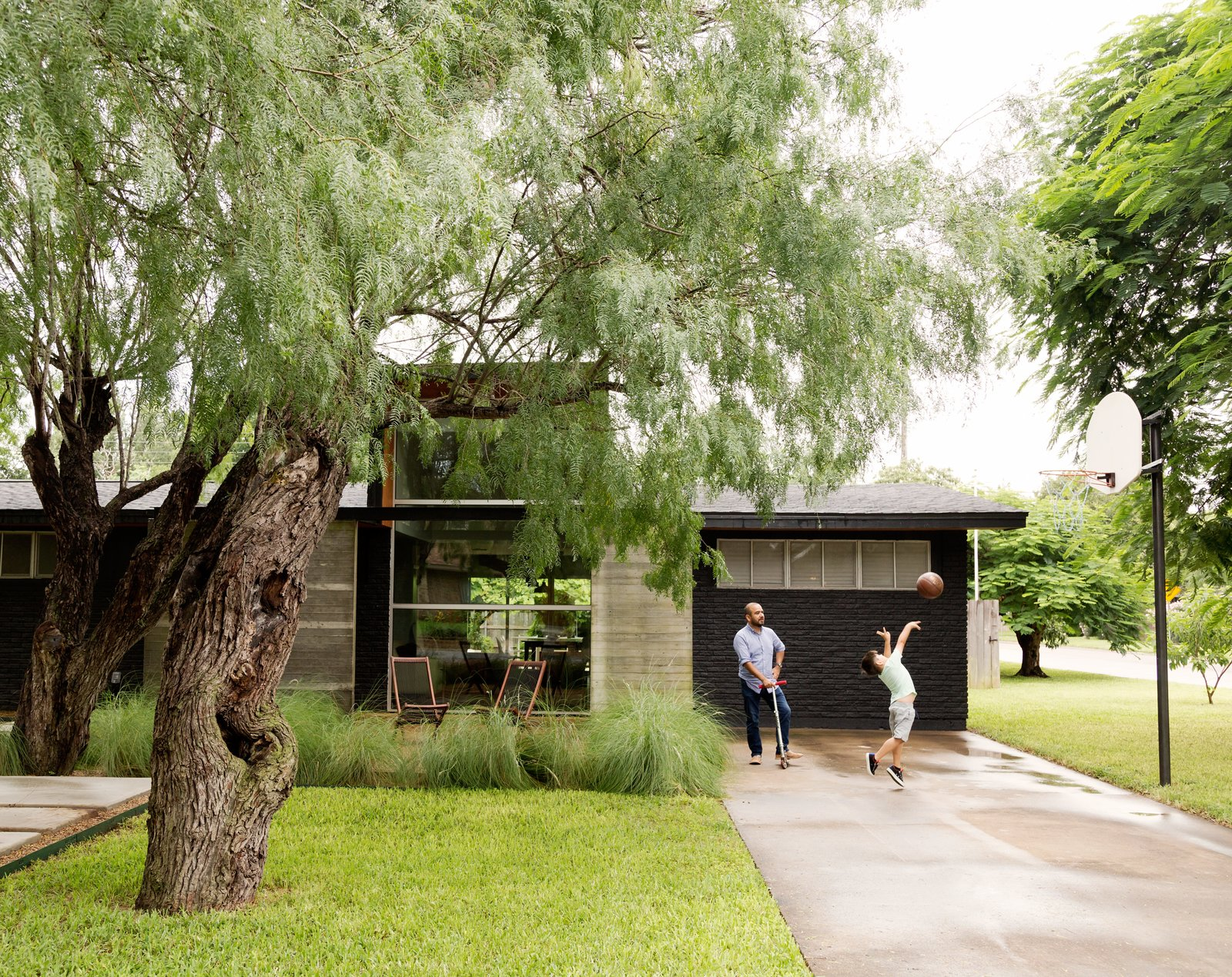 Exterior, Concrete Siding Material, and Brick Siding Material López insisted on a concrete pathway that winds through the trees, so visitors don't have to enter through the driveway.  Photo 2 of 10 in A Modern Renovation Connects to a Traditional Texas Town Through a Glass Wall