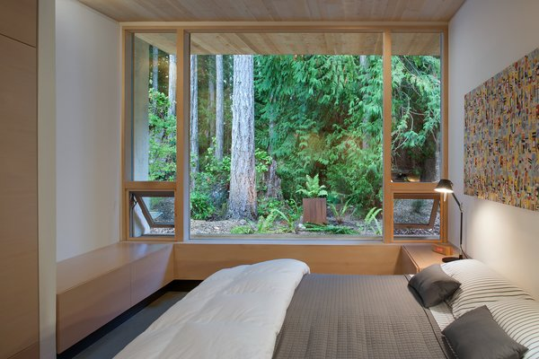 """""""You go down a hall and turn left to go to bed, to block noise from the living room,"""" Jones says. """"And each space in the house looks out onto something different, in all directions."""" The bed is custom-made by Jones, which is covered with linens from Bespoke Design in Victoria, B.C. A black Tolomeo mini table lamp sits on the nightstand."""