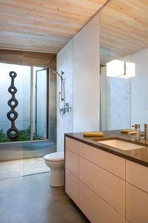A Toto toilet and bathroom sink, with a faucet by GROHE, are illuminated by a Leucos light fixture. Birgit Piskor designed the sculpture in the garden beside the shower.