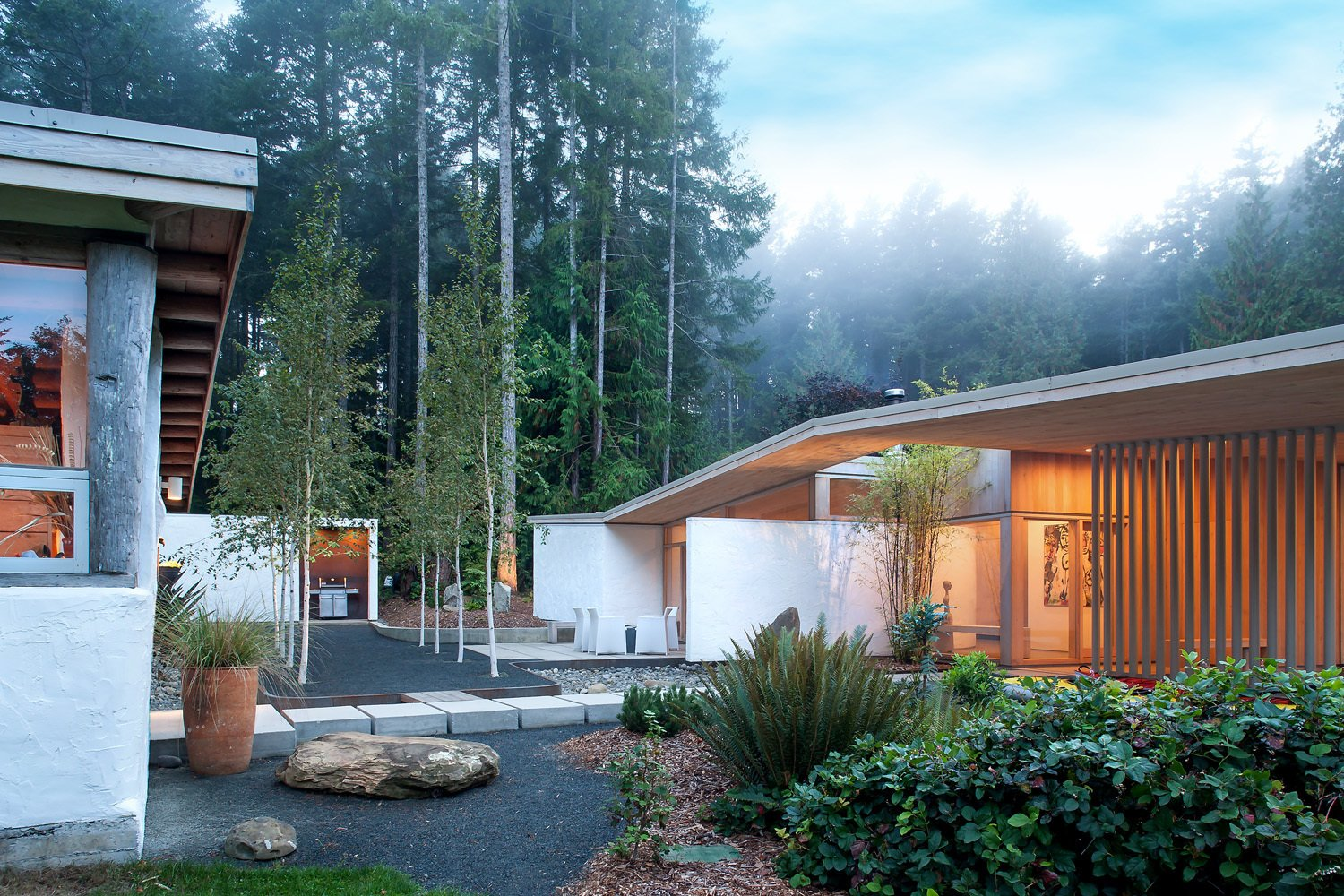 """""""The new house is not shy to look across at the old house, where you can see old rough stucco on one building, and then the same stucco on our new building,"""" Jones says. Tagged: Exterior, House, and Stucco Siding Material.  Super Secluded Homes by Luke Hopping from A Couple's Cherished Vacation Home is Given a Second Life"""